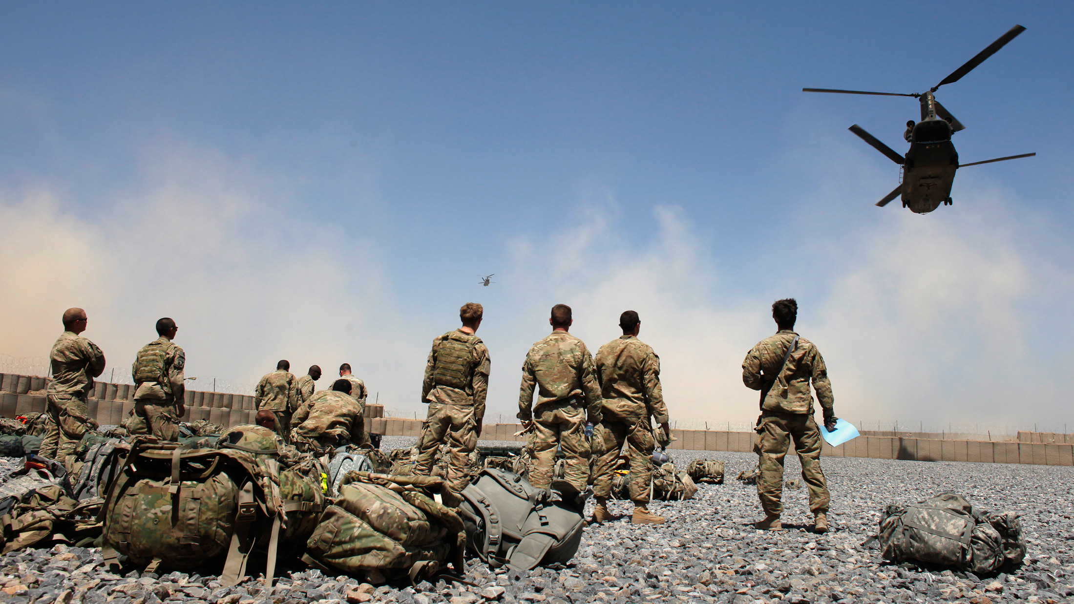 U.S. Army soldiers from the 1-320 Field Artillery Regiment, 101st Airborne Division, watch helicopters at Combat Outpost Terra Nova
